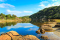River scape with rocks in foreground and blue water and sky australian Royalty Free Stock Images