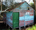 River shack a broken down old shed nestled into the banks of a mangrove riddled bank old with a relatively new green door Stock Photo