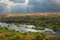 River in spate after a storm flowing through lush green countryside under stormy black sky Stock Photography