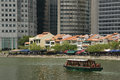 River taxi boat quay singapore passing old heritage houses and modern skyscrapers at Royalty Free Stock Photography