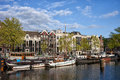 River view of amsterdam terraced houses boats and barges along amstel in the netherlands Stock Image
