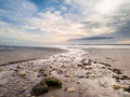 River winding across flat deserted beach to sea Royalty Free Stock Photo