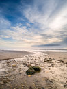 River winding across flat deserted beach to sea Stock Image
