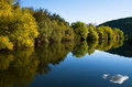 Riverbank tree line and river reflection Stock Photography
