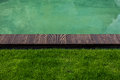 Riverbank with wooden path and green lawn closeup shot of Stock Image