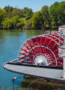 Riverboat paddle wheel in a river red with trees Stock Photos