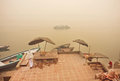 Riverboats in fog of morning scene on Ganges river with old docks and boats Royalty Free Stock Photo