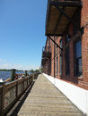 Riverwalk in wilmington north carolina stretch of boardwalk historic nc with old mills brick warehouses on the right and the cape Stock Photo