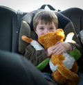 On the road again child in car seat a young boy with his favorite stuffed animal heading out Stock Photography