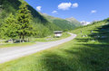 Road in alpine meadow landscape of high mountains on a clear summer sunny day northern italy Royalty Free Stock Image