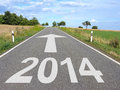 Road with arrow to year through agricultural landscape white marking on tarmac of and large pointing the horizon Stock Images