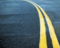 The road a blacktop covered with two yellow lines recedes into distance Royalty Free Stock Photos