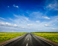 Road in blooming spring meadow travel concept background Stock Photo