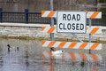 Road closed due to flash flooding ducks swim on a flooded street next a orange and white sign Stock Photos