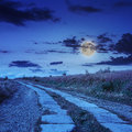Road of concrete slabs uphill to the night sky through field turns in moon light Stock Photo