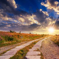 Road of concrete slabs uphill to the sunset sky through field turns at Stock Images