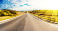 Road in countryside scenic view of receding through with sun shining background Royalty Free Stock Photos