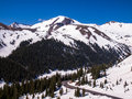 Road curving through snow covered mountains independence pass in colorado one of the nations highest mountain passes drops back Royalty Free Stock Photo