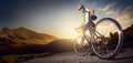 Road cyclist stand on the in mountain sunset landscape Stock Photography