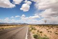 Road in a desert with beautiful blue sky full of clouds Stock Image