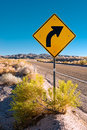Road in the desert and turn sign Stock Photo