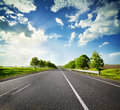 Road with a dividing strip under blue cloudy sky Royalty Free Stock Images