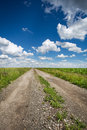 Road in field and blue sky with clouds Stock Photography