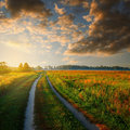 Road in field and cloudy sky Royalty Free Stock Photo
