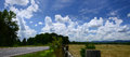 Road and Field Under Fluffy Clouds in Blue Sky Royalty Free Stock Images