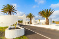 Road and gate to costa teguise town with palm trees white entry lanzarote canary islands spain Stock Photos