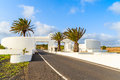 Road and gate to costa teguise town with palm trees white entry lanzarote canary islands spain Stock Images
