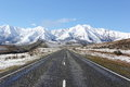 A road heading towards the snowy mountains of canterbury new zealand Stock Image