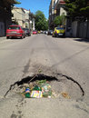 Road hole full of garbage on a street in bucharest Royalty Free Stock Photography