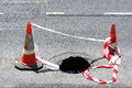 Road hole with warning cones and tape Royalty Free Stock Photo