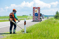 Road landscapers cutting grass around mileposts Royalty Free Stock Photo