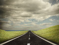 Road leading out to the horizon under clouds Stock Photos