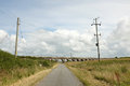 Road leading to bridge a single track with flanking posts and power cables leads an arched in the distance Royalty Free Stock Images