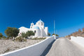 Road leading to church on santorini greece island cyclades sunshine with cloudless blue sky moon is visible top Royalty Free Stock Images