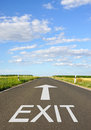 Road marked exit long straight tarmac with green fields on either side with text in bold uppercase white letters and with arrow Stock Photography