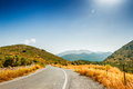 Road between the mountains and groves of olive trees. Royalty Free Stock Photo
