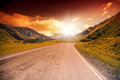 Road in the mountains landscape with bright sunset