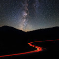 Road in the mountains under milky way Stock Photos