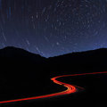 Road in the mountains under a starry gyres Stock Photos