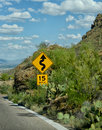 Road 15 mph sign warning of curves in the road ahead Royalty Free Stock Photo