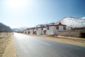 On the road nyingchi tibet driving highway to at early spring time small village with snowy mountain as background china Royalty Free Stock Photography