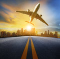 Road perspective to town and passenger plane flying above,air tr Royalty Free Stock Photo