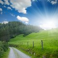 Road photo of and meadow with blue sky and sun glow Stock Photo