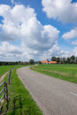 Road running thru landscape dutch beautifull big clouds in the blue sky Royalty Free Stock Photos