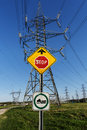Road sign electrical towers power line beside a bridge on a bright blue sky Stock Photo