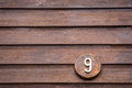 Road sign on a house reading the number nine made out of wood Royalty Free Stock Photo